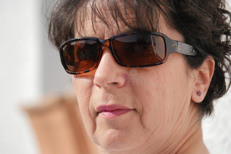 Porträt der reifen Frau des Brunette mit Sonnenbrille stockbilder