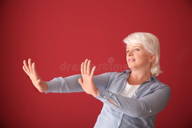 Porträt der reifen Frau etwas auf Farbhintergrund zurückweisend lizenzfreies stockfoto