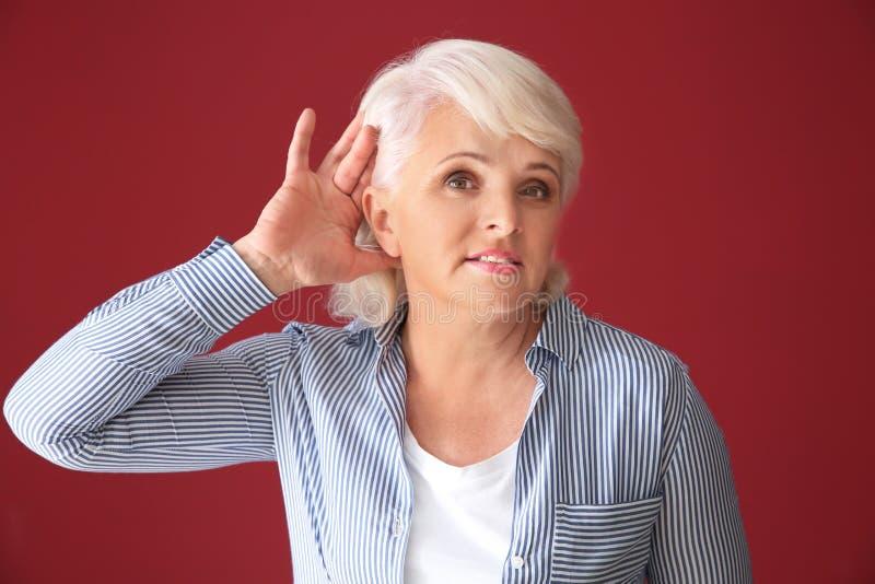 Porträt der reifen Frau versuchend, etwas auf Farbhintergrund zu hören stockbilder