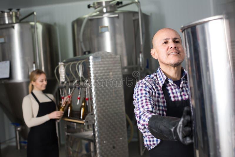 Porträt der reifen frohen männlichen Brauereiarbeitskraft stockbilder