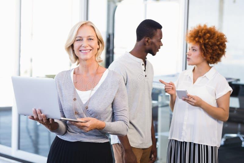 Porträt der reifen Geschäftsfrau mit Kollegen im Hintergrund lizenzfreies stockfoto