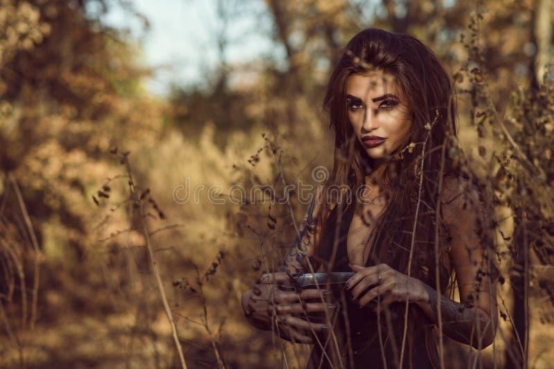 Porträt der reizend gefährlichen jungen Hexe, die im Wald einen Topf mit Zaubertrank hält und gerade mit Durchdringungsanstarren  stockbild