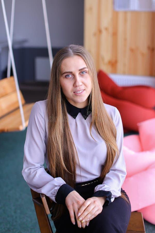 Porträt der reizend jungen Geschäftsfrau, die Kamera mit betrachtet lizenzfreie stockfotos