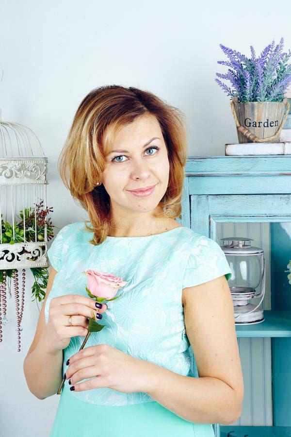 Porträt der reizend mittleren erwachsenen Frau in der blauen Kleiderholding stieg lizenzfreies stockfoto