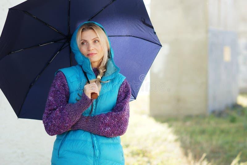 Porträt der reizenden reifen blonden Frau mit Regenschirm lizenzfreie stockfotos