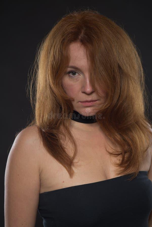 Porträt der ruhigen Frau im bloßen Schulterschwarzkleid lizenzfreies stockbild
