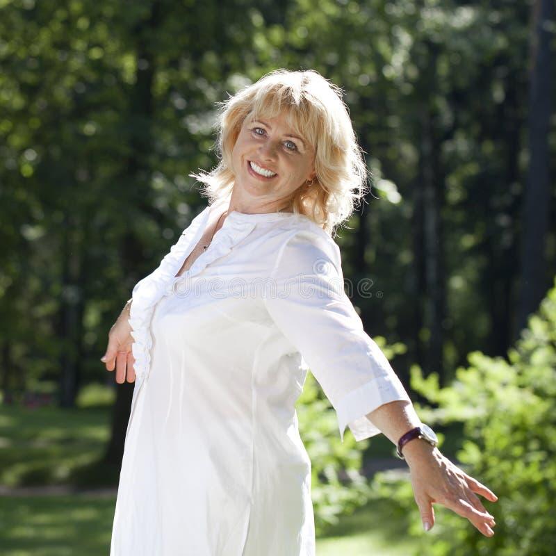 Porträt der ruhigen reifen Frau im Sommerpark stockfotos