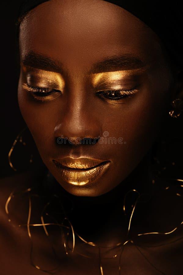 """Porträt der schönen afrikanischen Frau mit kreativem Gold-make†""""oben und Schmuck lizenzfreie stockfotografie"""