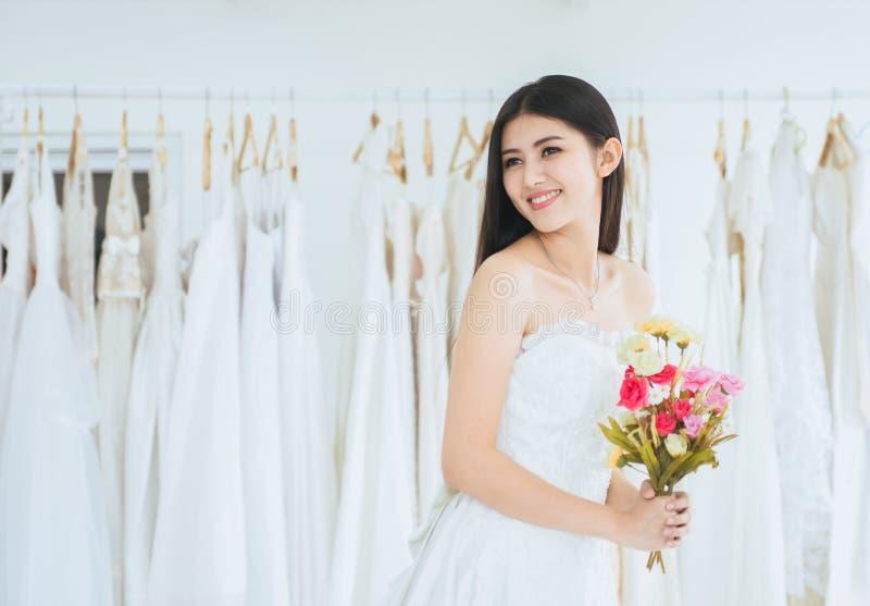 Porträt der schönen asiatischen Frauenbraut in der weißen Heiratskleiderholdingblume und Lächeln lizenzfreie stockfotos