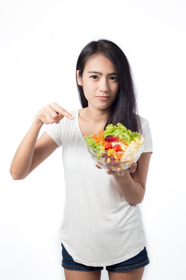 Porträt der schönen asiatischen jungen Frau, die Gemüsesalat isst stockfotografie
