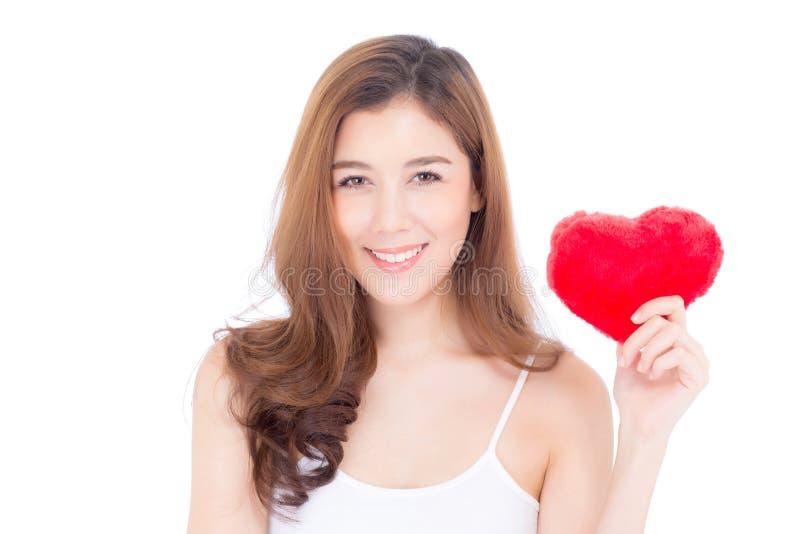 Porträt der schönen asiatischen jungen Frau, die rotes Herzformkissen hält stockbilder
