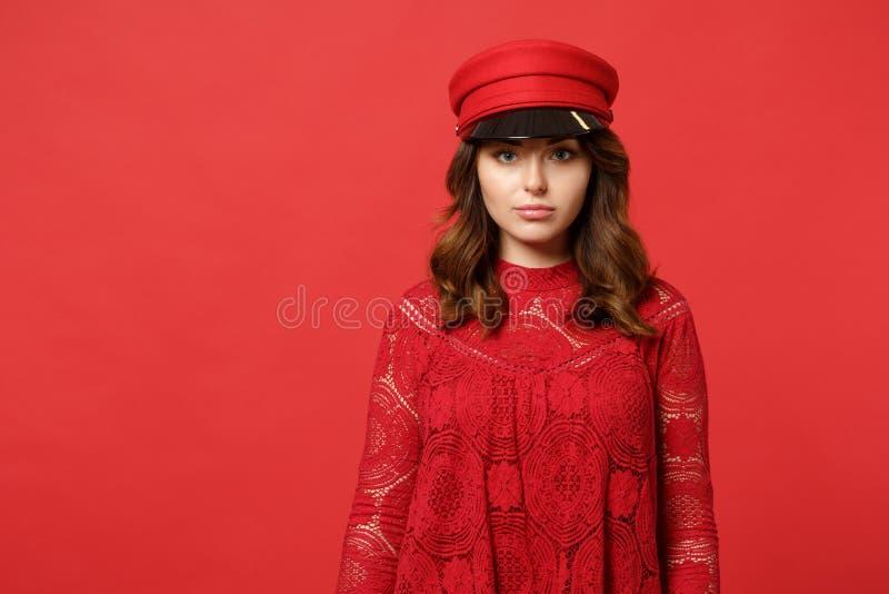 Porträt der schönen attraktiven jungen Frau im Spitzekleid, Kappenstellung, welche die Kamera lokalisiert auf heller roter Wand s lizenzfreies stockbild