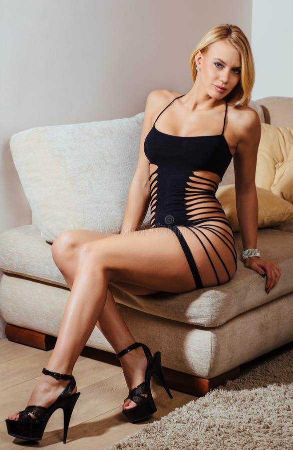 Porträt der schönen blonden Frau, die auf Couch sich entspannt stockbild