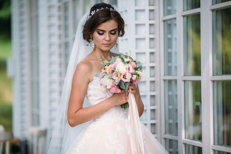 Porträt der schönen Braut mit Blumenstraußblumen im weißen Luxuskleid Herrliches Modell mit Brautmake-up und Frisur stockfoto