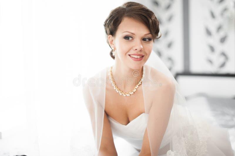 Porträt der schönen Braut mit dem Modeschleier, der zu Hause an aufwirft lizenzfreie stockfotos