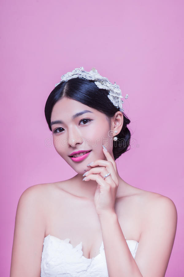 Porträt der schönen Braut mit der Hand auf Kinn gegen rosa Hintergrund stockfoto
