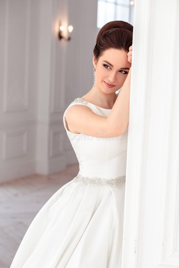 Porträt der schönen Brunettebraut mit eleganter Frisur und dem Make-up, die langes Luxushochzeitskleid trägt stockbild