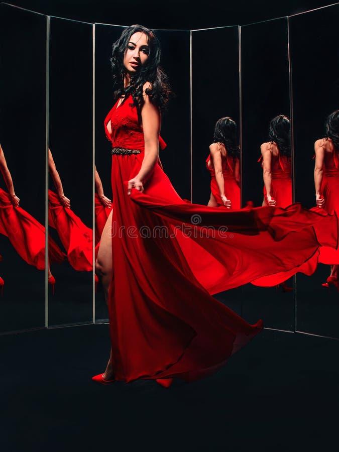 Porträt der schönen Brunettefrau in den roten im herum drehenden und tanzenden Schuhen und Kleid stockfoto