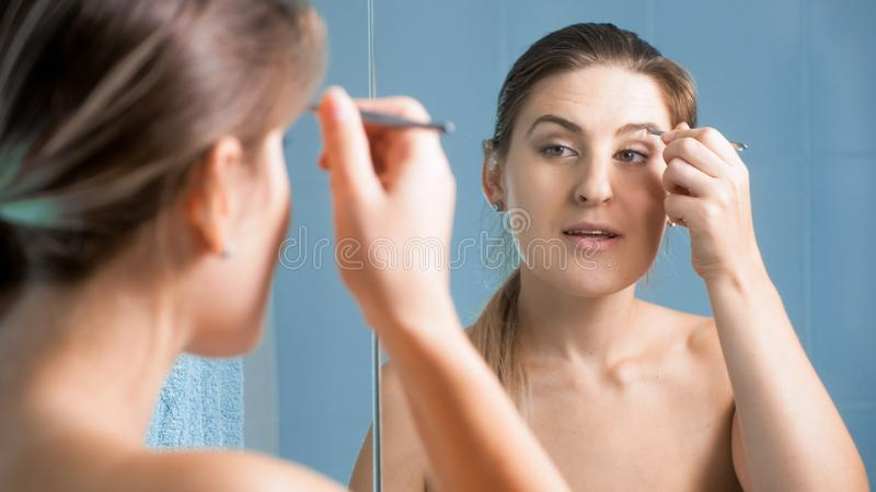 Porträt der schönen Brunettefrau, die Augenbrauen mit Pinzette zupft stockfotos