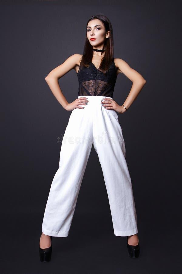 Porträt der schönen Brunettefrau in einer schwarzen Bluse und in weißen Hosen, Modefotoschuß stockfoto