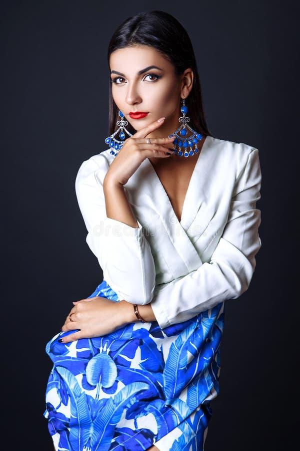 Porträt der schönen Brunettefrau in einer weißen Bluse und in einem blauen Rock Modefotoschuß lizenzfreies stockbild