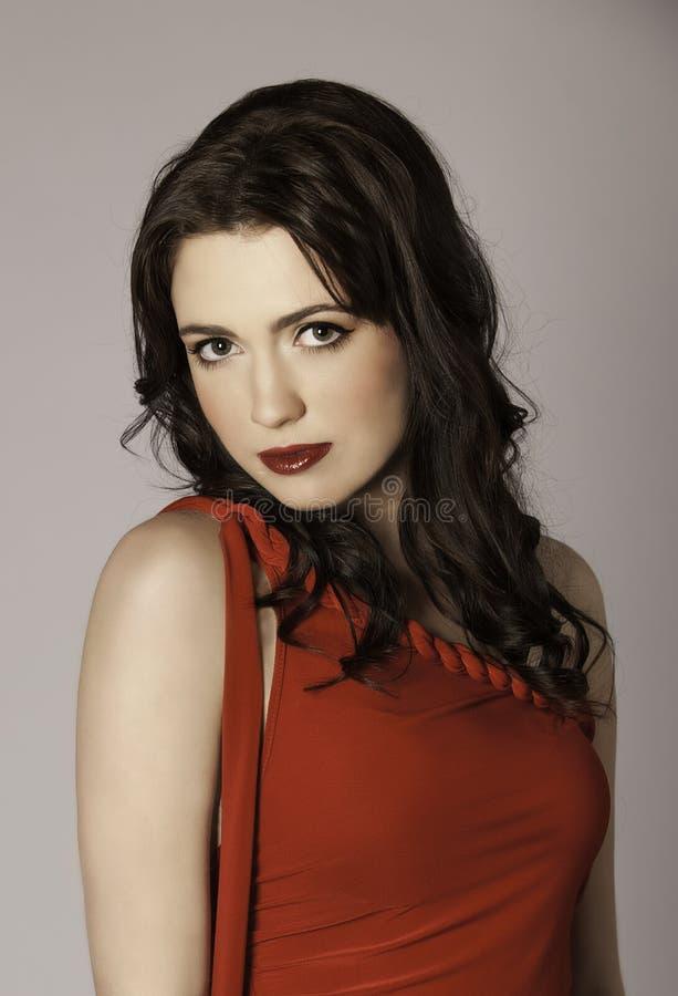 Porträt der schönen Brunettefrau im Rot lizenzfreie stockfotografie