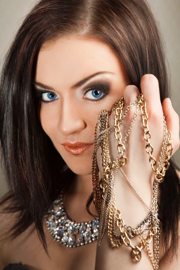 Porträt der schönen Brunettefrau im Schmuck lizenzfreies stockbild