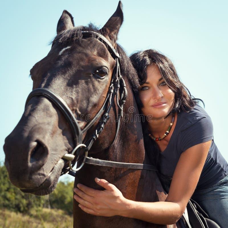 Porträt der schönen dunkelhaarigen Frau auf einem Pferd stockbild