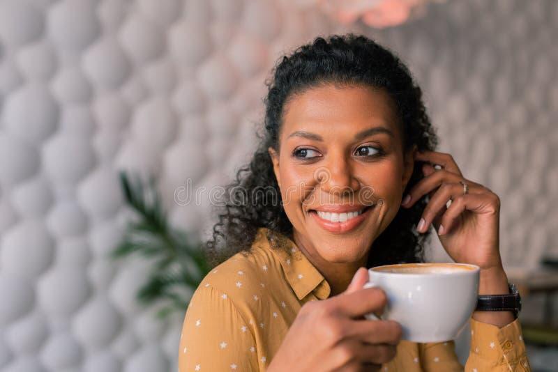 Porträt der schönen dunkelhaarigen gelockten Frau, die ihren Tasse Kaffee genießt lizenzfreie stockbilder
