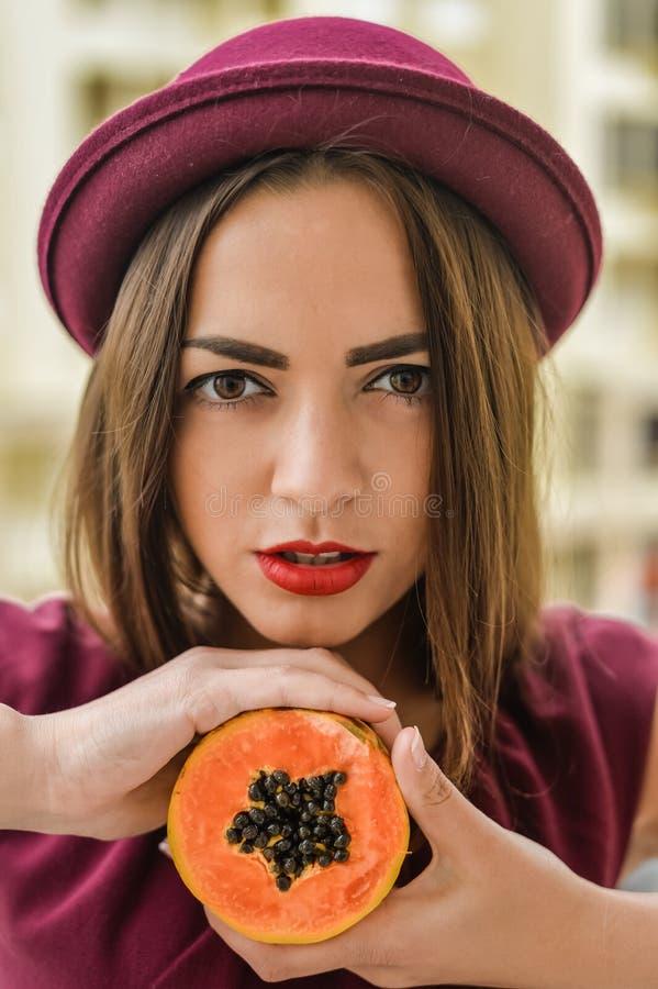 Porträt der schönen eleganten Frau, die den roten geglaubten Hut hält Hälfte der Papayafrucht nahe bei ihrem Gesicht trägt lizenzfreie stockfotografie