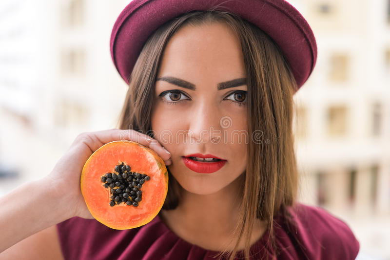 Porträt der schönen eleganten Frau, die den roten geglaubten Hut hält Hälfte der Papayafrucht nahe bei ihrem Gesicht trägt lizenzfreie stockbilder
