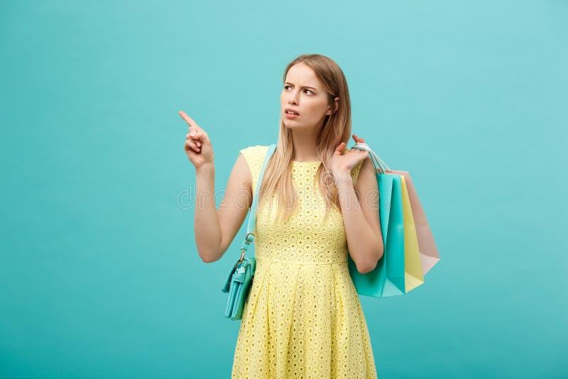 Porträt der schönen ernsten jungen Frau mit Einkaufstasche über blauem Studiohintergrund lizenzfreie stockfotografie