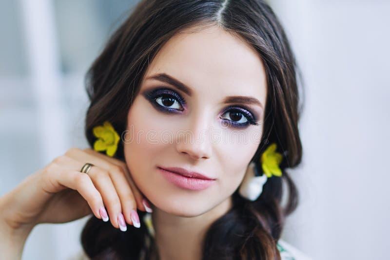 Porträt der schönen europäischen Frau in den gelben earings in der weißen Wohnung, recht junge Frau mit dem dunklen Haar im Licht lizenzfreie stockfotografie
