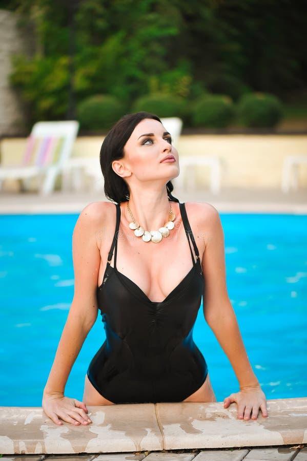 Porträt der schönen gebräunten Frau in der schwarzen Badebekleidung, die im Swimmingpoolbadekurort sich entspannt lizenzfreie stockfotos