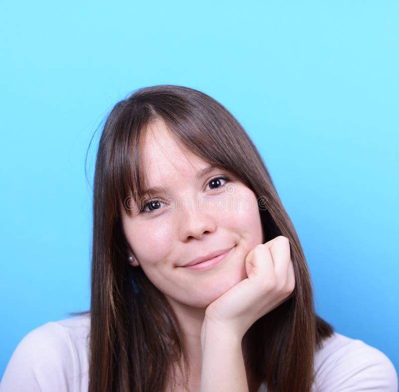 Porträt der schönen glücklichen Frau gegen blauen Hintergrund stockfotografie