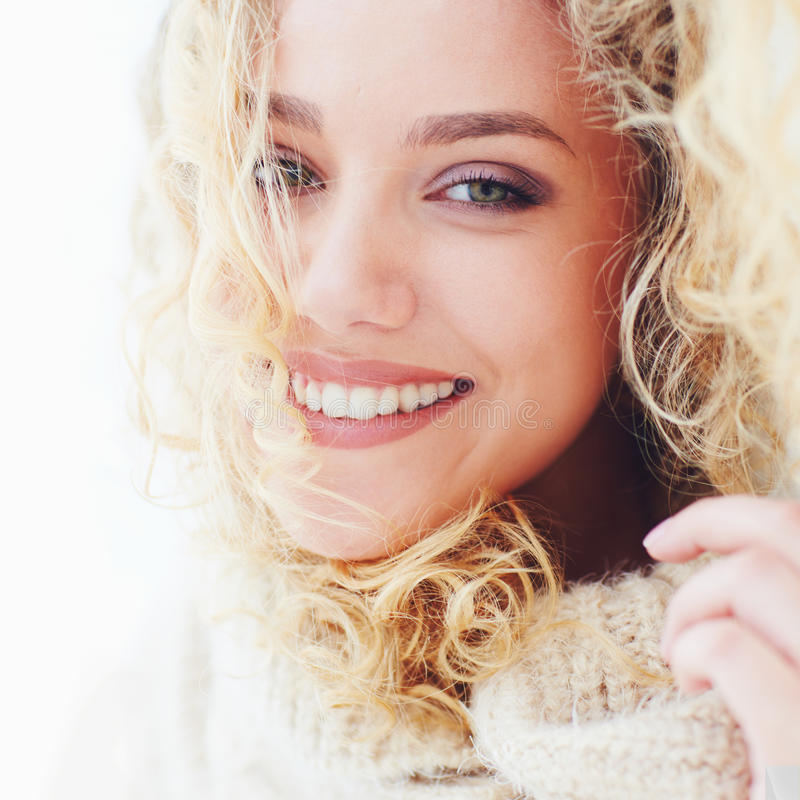 Porträt der schönen glücklichen Frau mit dem gelockten Haar und entzückendem Lächeln lizenzfreie stockfotografie