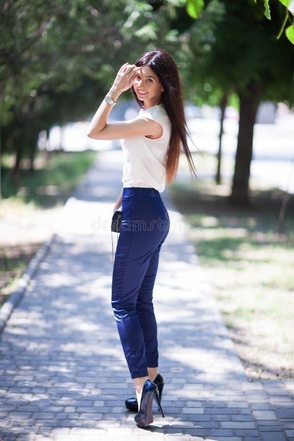 Porträt der schönen glücklichen stilvollen Frau mit dem langen Haar in den Schuhen der hohen Absätze, gehend in Stadtpark Frauena lizenzfreies stockbild