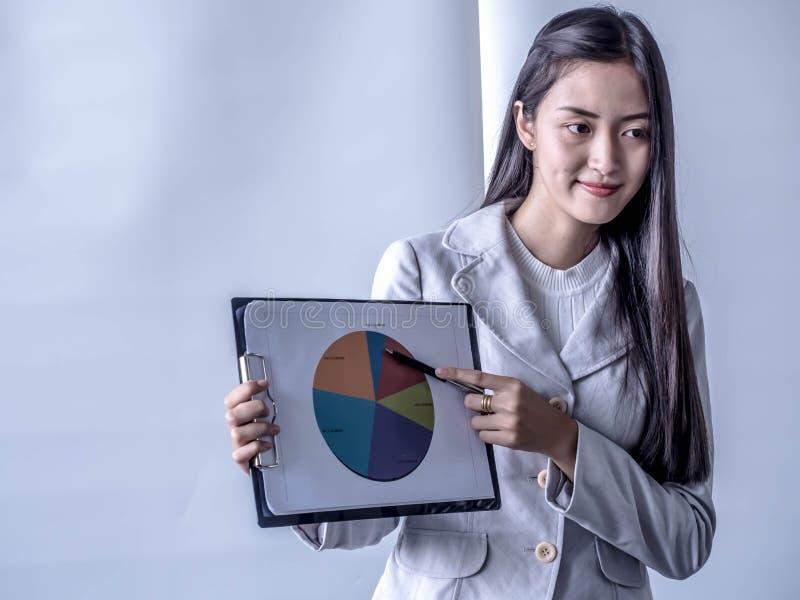 Porträt der schönen Interniertstellung im Büro vor Flip-Chart und des Darstellens im Konferenzzimmer stockfotografie