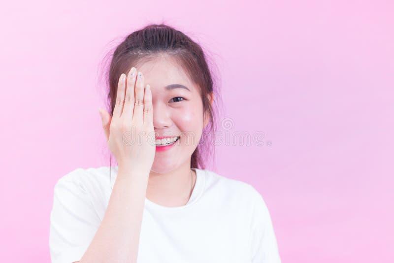 Porträt der schönen jungen Abnutzung des schwarzen Haares der Asiatin eine weiße T-Shirt Bedeckung mit den Händen ihr Auge und Lä lizenzfreie stockbilder