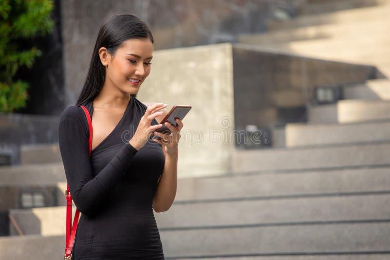 Porträt der schönen jungen asiatischen Geschäftsfrau im schwarzen Kleid nennend mit Smartphonestellung in der Stadt Gl?ckliche el lizenzfreie stockfotos