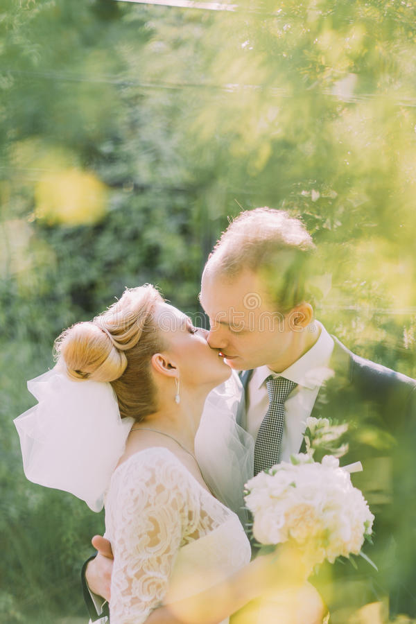 Porträt der schönen jungen blonden Braut und glücklichen des Bräutigams, die draußen an ihrem Hochzeitstag küsst lizenzfreies stockbild