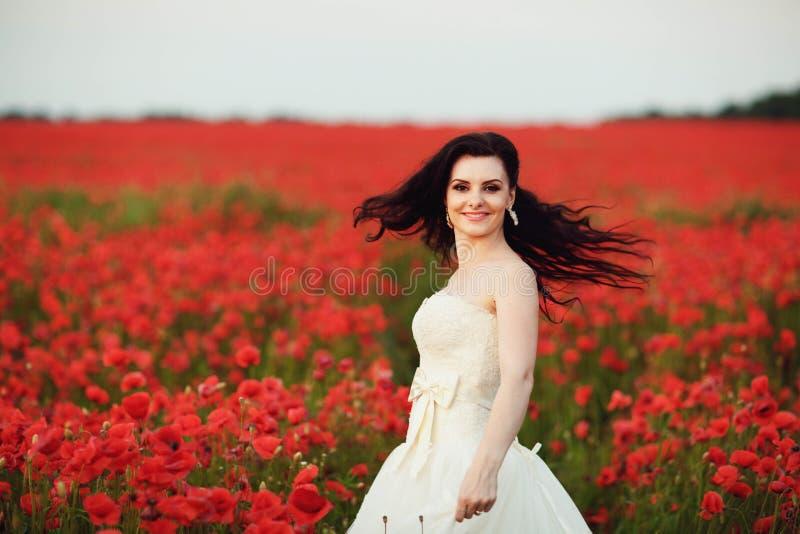 Porträt der schönen jungen Braut auf dem Gebiet voll von roten Mohnblumen stockbilder