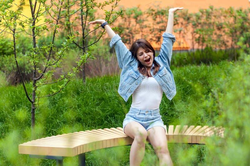 Porträt der schönen jungen brunette Frau im blauen zufälligen Denimartsitzen und Frühling im im Freien, gähnend mit geschlossenen stockbild
