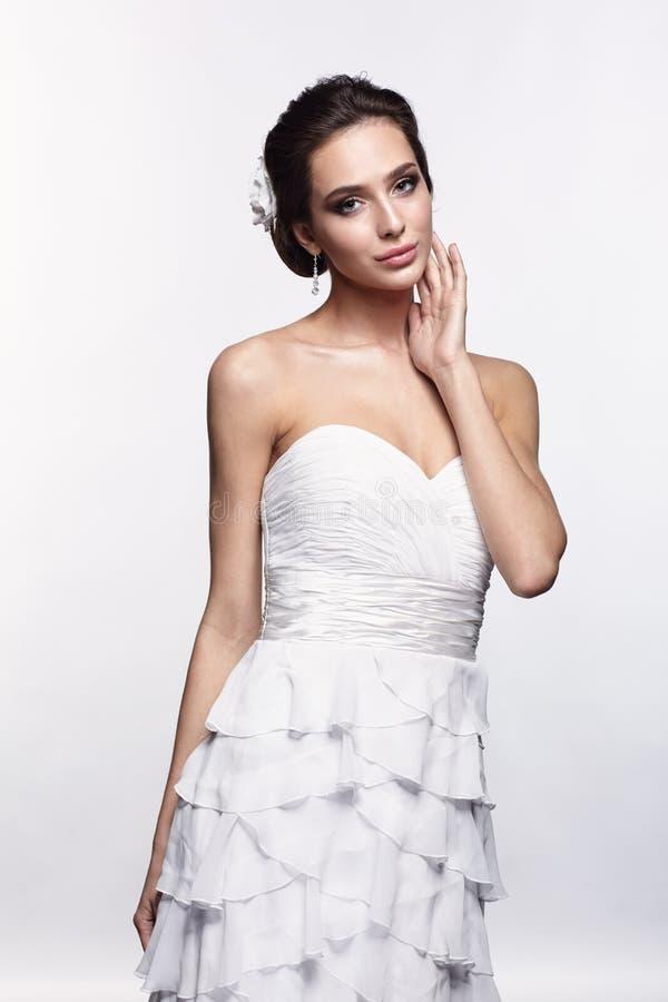 Porträt der schönen jungen Brunettefrauenbraut in weißem Weddin lizenzfreie stockfotografie