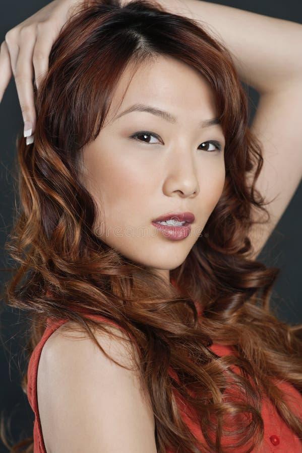Porträt der schönen jungen Chinesin mit der Hand im Haar stockfotografie