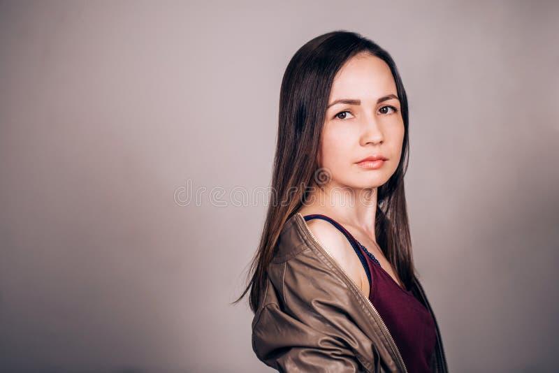 Porträt der schönen jungen Frau auf grauem Hintergrund Ernstes Gesicht lizenzfreie stockbilder