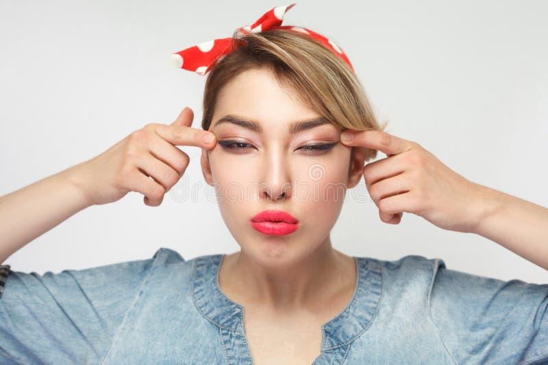 Porträt der schönen jungen Frau der Blindheit im zufälligen blauen Denimhemd mit Make-up und roter Stirnbandstellung, dehnt Augen stockfotos