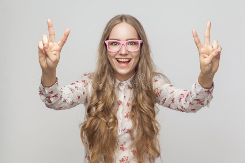 Porträt der schönen jungen Frau, die Friedenszeichen zeigt und toothy lizenzfreies stockfoto