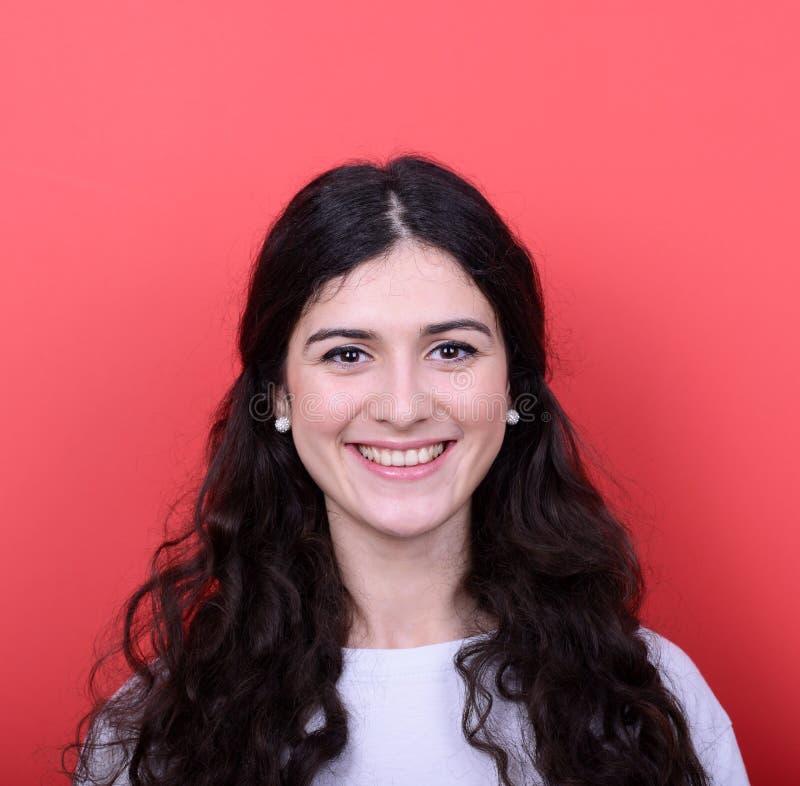 Porträt der schönen jungen Frau, die gegen roten Hintergrund lächelt stockbild