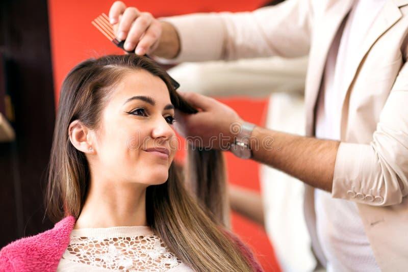 Porträt der schönen jungen Frau, die Haarschnitt erhält lizenzfreie stockfotografie